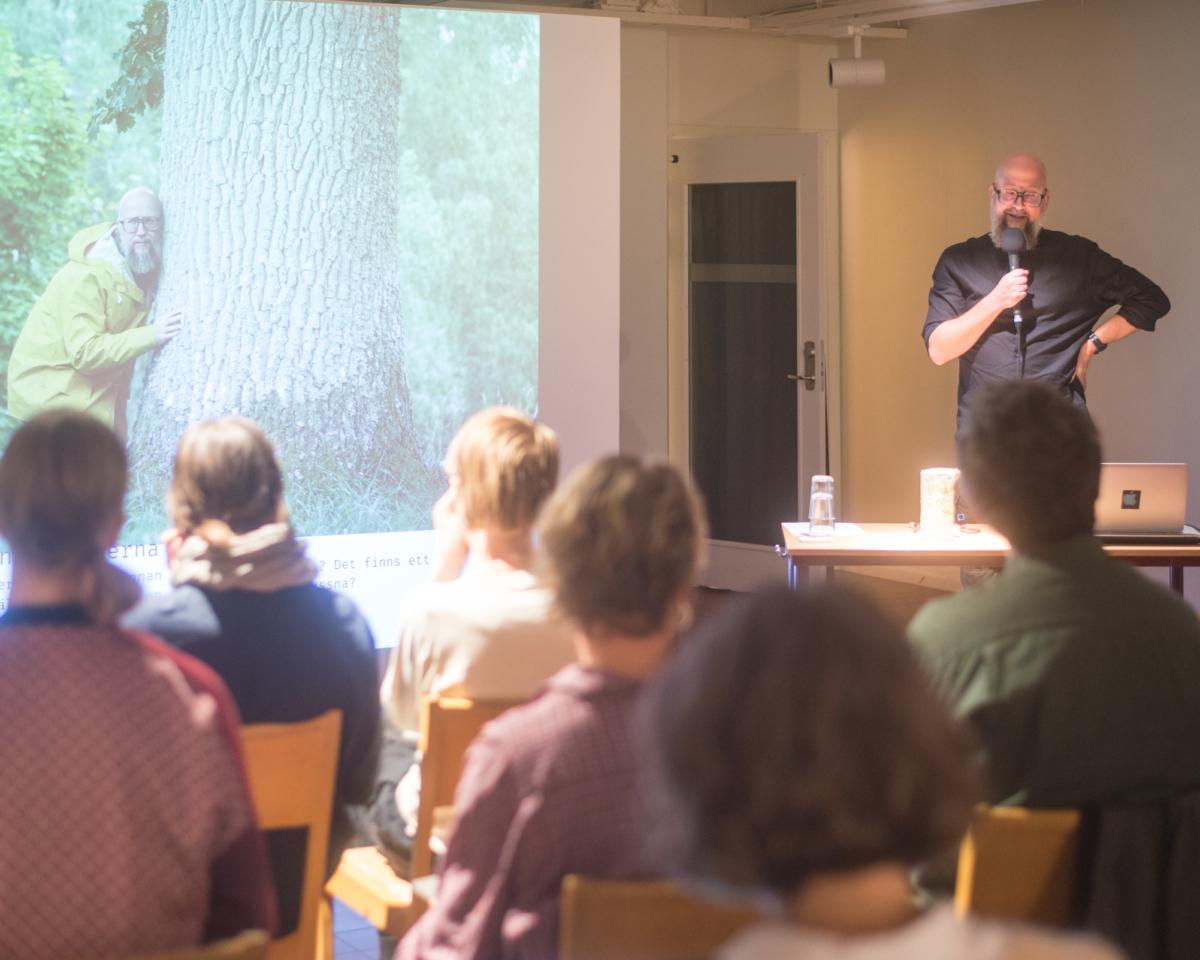 Man står framför en skärm och håller en presentation. På bilden syns samme man som lyssnar med örat mot ett träd.