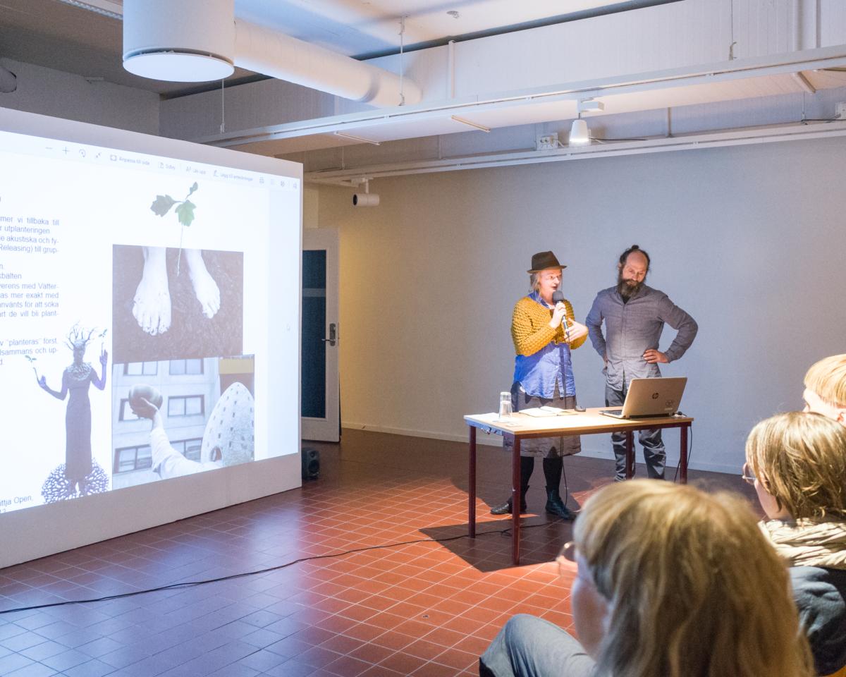 Man och kvinna håller en presentation framför publik.