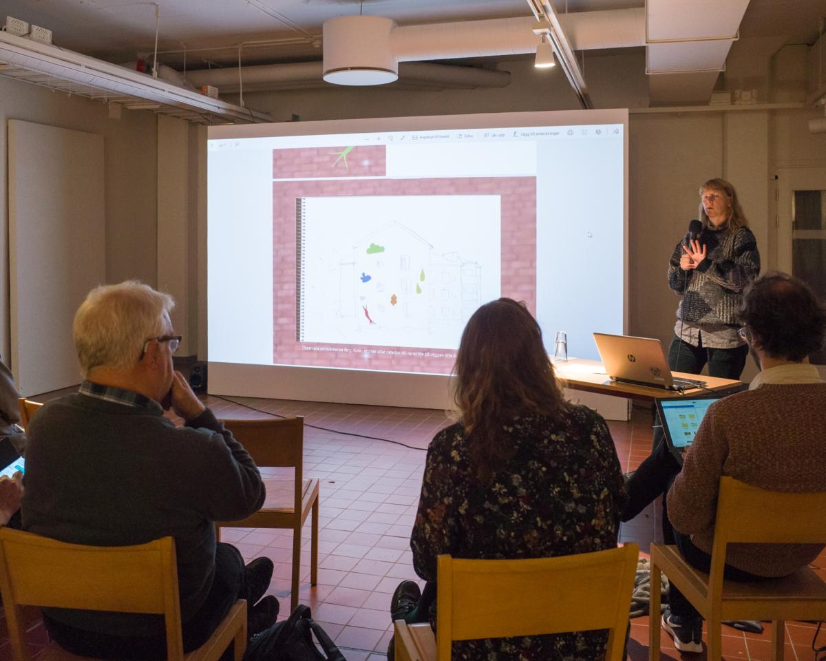 Kvinna står framför publik och håller en presentation.