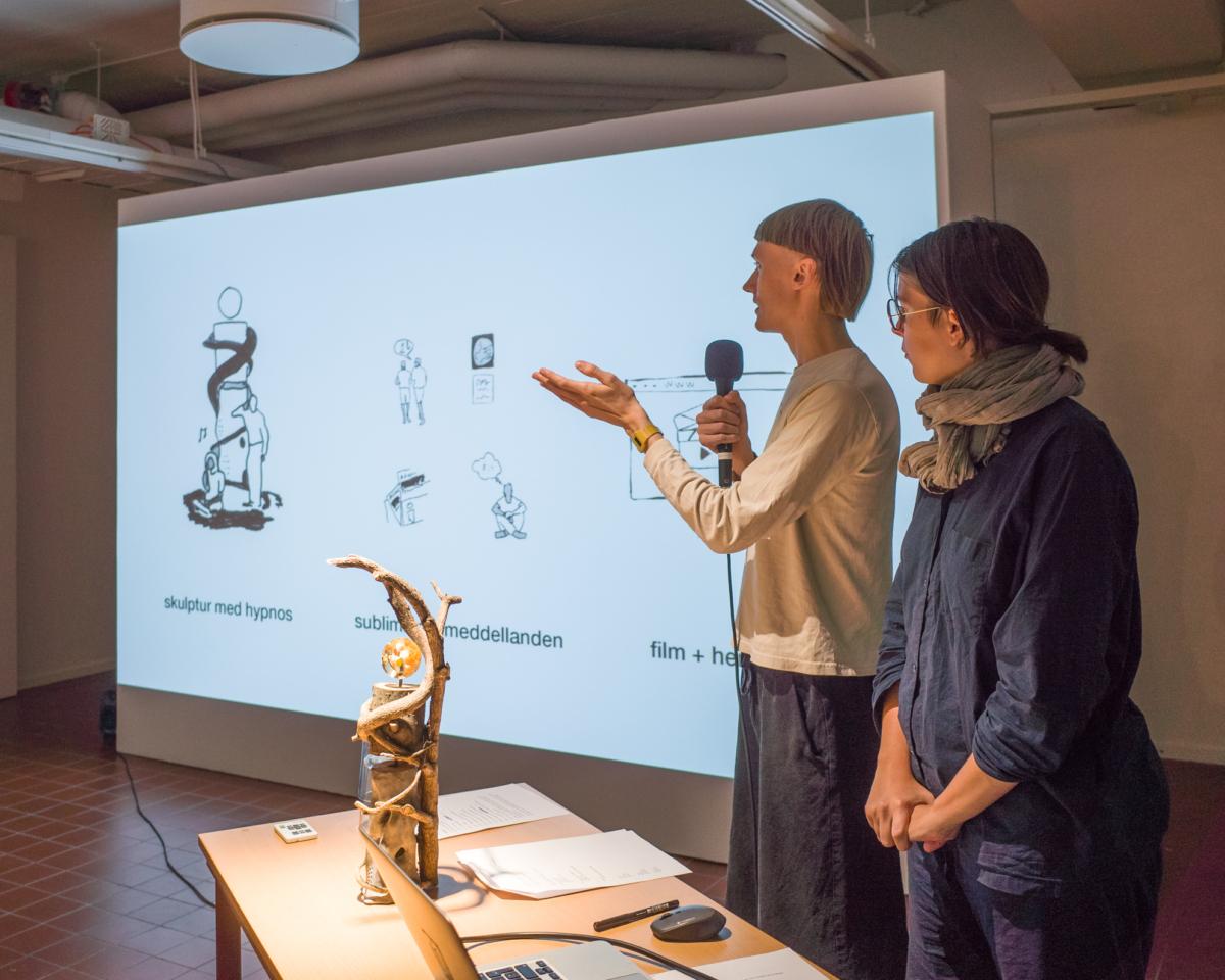 Man och kvinna står framför en skärm och håller en presentation. På bordet framför dem står en modell av en skulptur.