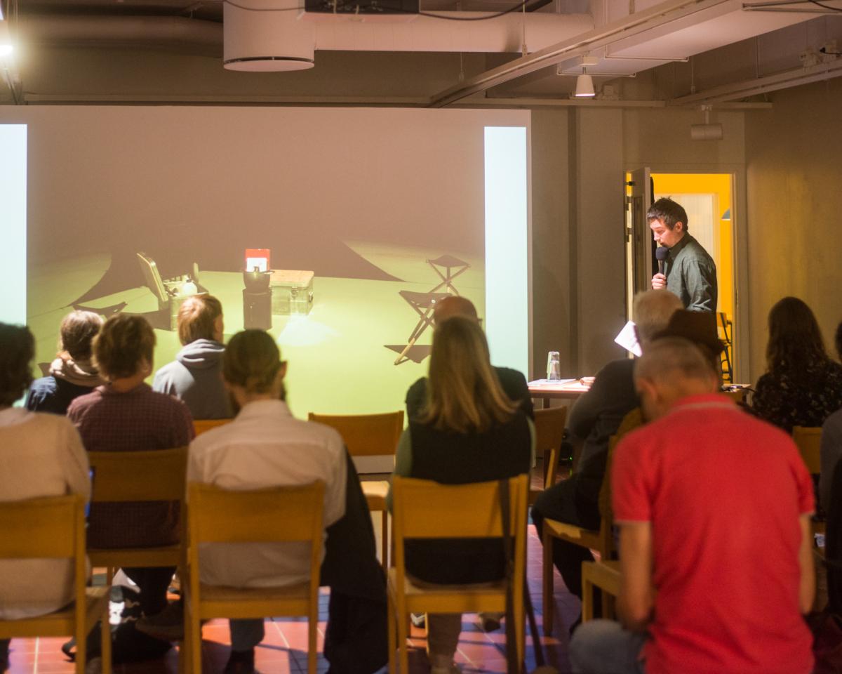 Man står framför publik och håller en presentation.