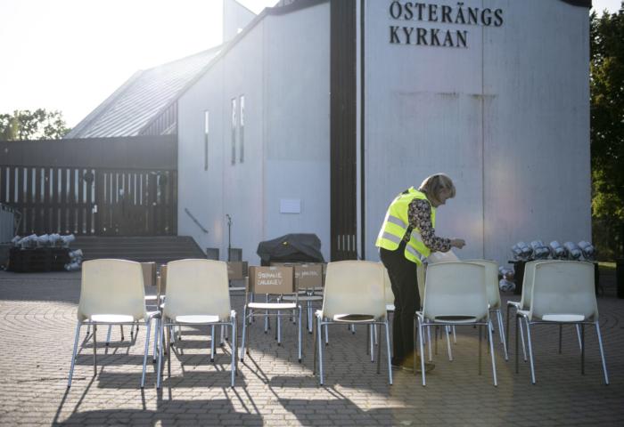 En kvinna i gul väst ställer ut stolar framför en kyrka.